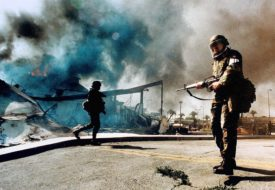[National Guardsmen patrol near Martin Luther King Blvd. and Vermont Avenue as a mini-mart burns in Los Angeles on May 1, 1992.]